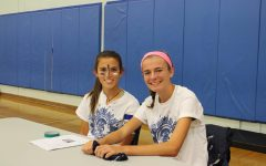 Students Noelia Aguirre and Paige Johnson show their school spirit by wearing blue and white.